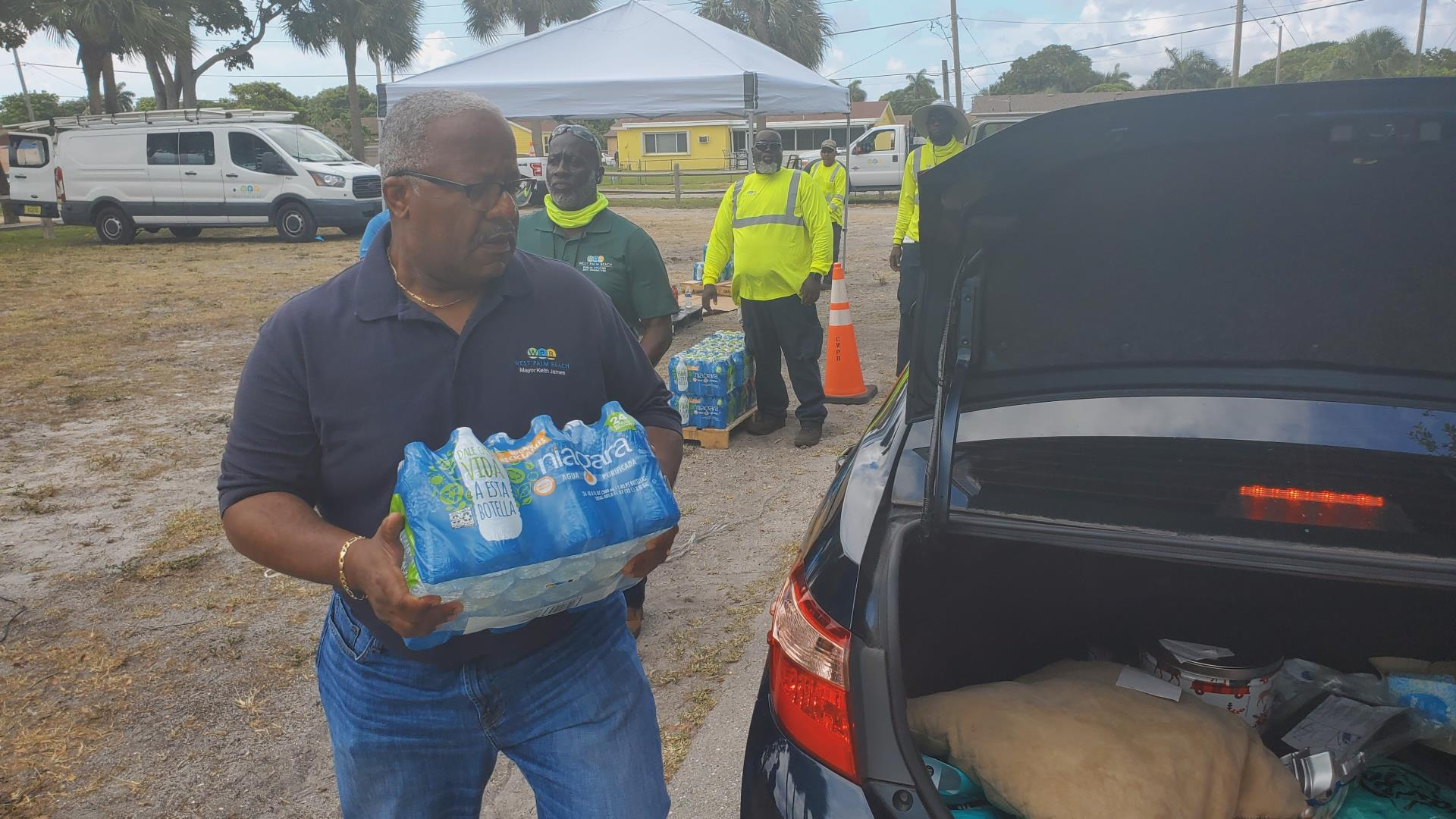 Mayor Keith A. James loads drinking water into the cars of residents from the City distribution point in Gaines Park Monday